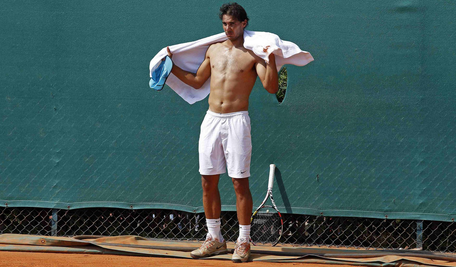 Rafael Nadal of Spain uses a towel to dry off during a training session at the Monte Carlo Masters in Monaco April 14, 2014. REUTERS/Eric Gaillard (MONACO - Tags: SPORT TENNIS)