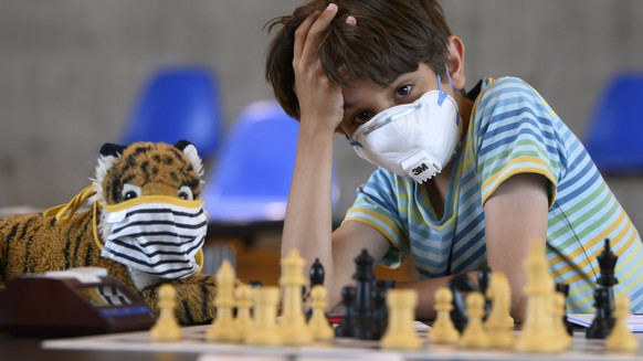 BILD DER WOCHE NATIONAL - A young Chess player competes with a face mask, at the 53st Biel International Chess Festival, during the coronavirus disease (COVID-19) outbreak, in the Congress Center in Biel, Switzerland, on Tuesday, July 28, 2020. (KEYSTONE/Anthony Anex)