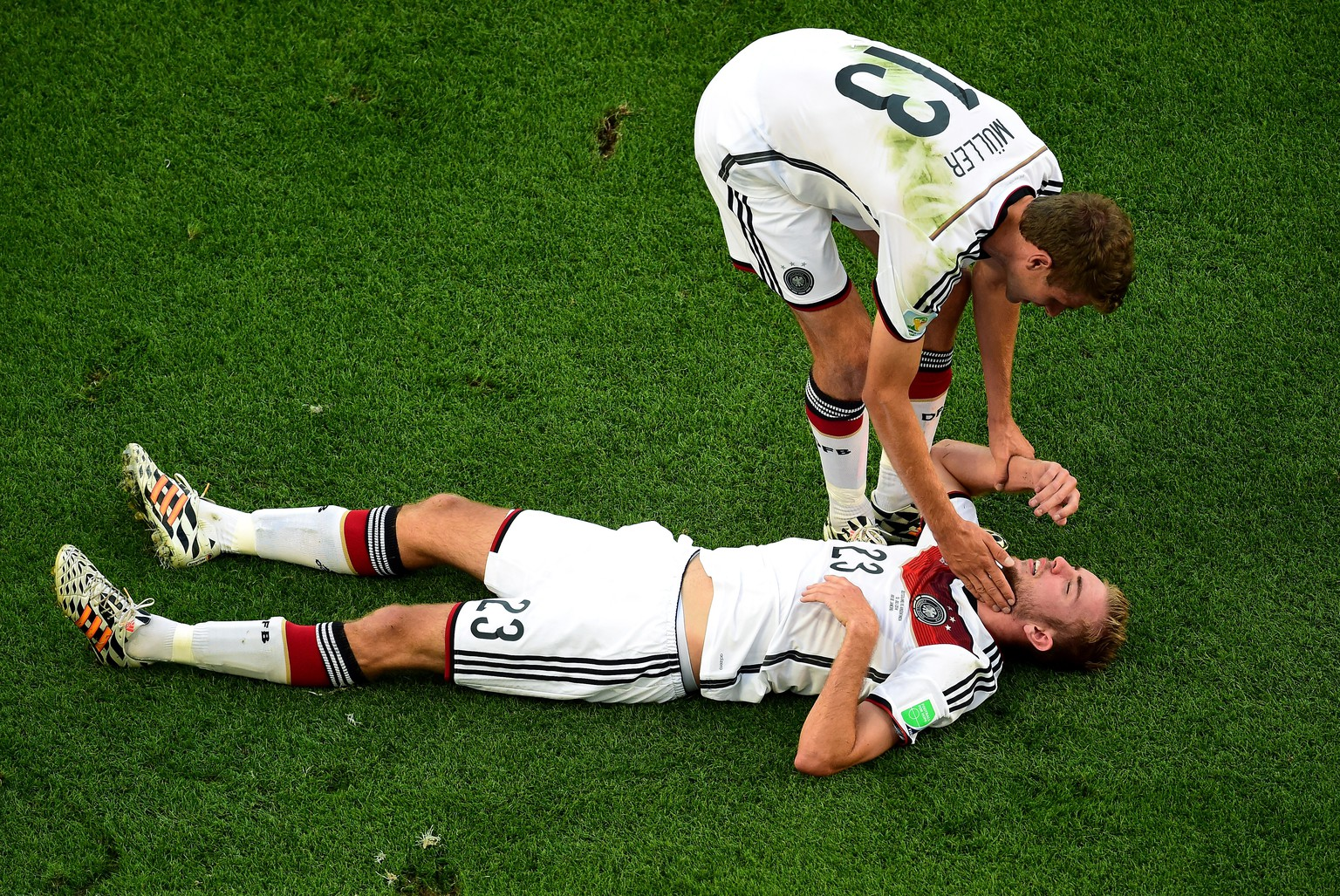 RIO DE JANEIRO, BRAZIL - JULY 13:  Christoph Kramer of Germany lies on the pitch as Thomas Mueller stands over during the 2014 FIFA World Cup Brazil Final match between Germany and Argentina at Maracana on July 13, 2014 in Rio de Janeiro, Brazil.  (Photo by Pool/Getty Images)