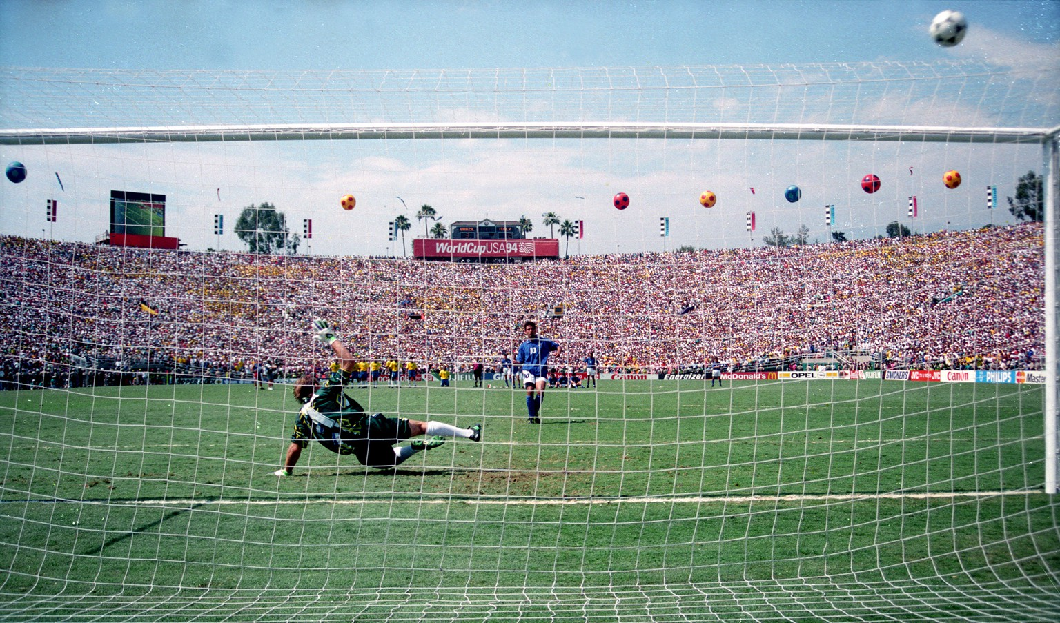 ITALY'S BAGGIO SENDS BALL OVER NET AS BRAZILIAN GOALKEEPER TAFARREL DIVES WRONG WAY DURING SHOOTOUT AT WORLD CUP IN PASADENA.  Italy's Roberto Baggio sends the ball over the net (R) as Brazilian goalkeeper Claudio Tafarrel dives the wrong way during a shootout to decide the World Cup in Pasadena, California, July 17, 1994. Brazil won its record fourth World Cup 3-2 on penalty kicks, the first time ever the World Cup final was decided in a penalty shootout. SCANNED FROM NEGATIVE REUTERS/Gary Hershorn - RTRUGAR