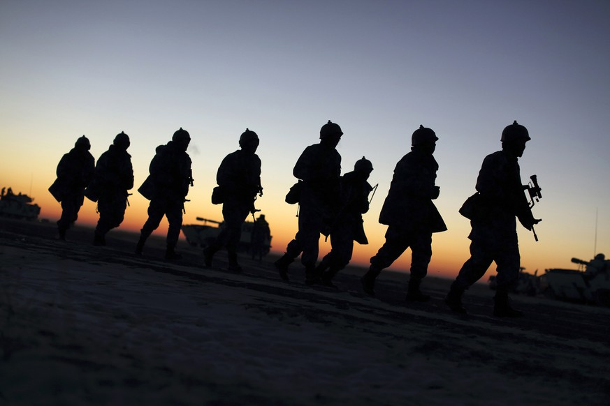 Soldiers of the People's Liberation Army (PLA) Marine Corps march during a military drill as the sun rises at a military base in Taonan, Jilin province January 28, 2015. Over 1,000 soldiers and 200 military vehicles from Chinese Marine Corps participated in this winter drill between January 8 to February 6, China Daily reported. Picture taken January 28, 2015. REUTERS/China Daily (CHINA - Tags: MILITARY ENVIRONMENT TPX IMAGES OF THE DAY) CHINA OUT. NO COMMERCIAL OR EDITORIAL SALES IN CHINA