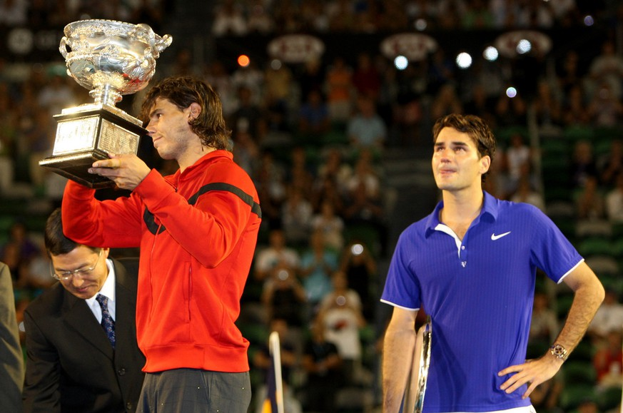 Spain's Rafael Nadal, left,  holds the trophy next to  runner-up Switzerland's Roger Federer  during the awarding ceremony of  the Men's singles final match at the Australian Open Tennis Championship  in Melbourne, Australia, Sunday, Feb. 1, 2009.  (AP Photo/Rick Stevens)