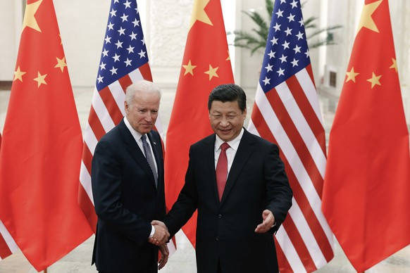 FILE - In this Dec. 4, 2013, file photo, Chinese President Xi Jinping, right, shakes hands with then U.S. Vice President Joe Biden as they pose for photos at the Great Hall of the People in Beijing. As Americans celebrate or fume over the new president-elect, many in Asia are waking up to the reality of a Joe Biden administration with decidedly mixed feelings. Relief and hopes of economic and environmental revival jostle with needling anxiety and fears of inattention. The two nations are inexorably entwined, economically and politically, even as the U.S. military presence in the Pacific chafes against China