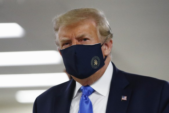 FILE - In this July 11, 2020, file photo President Donald Trump wears a face mask as he walks down a hallway during a visit to Walter Reed National Military Medical Center in Bethesda, Md. On Tuesday, July 21, Trump professed a newfound respect for the protective face masks he has seldom worn.