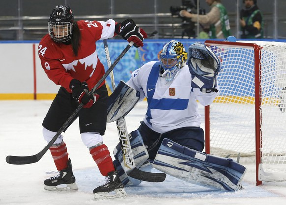Finland's goalie Noora Raty makes a save as she is screened by Canada's Natalie Spooner during the second period of their women's ice hockey game at the Sochi 2014 Winter Olympic Games, February 10, 2014. REUTERS/Mark Blinch (RUSSIA  - Tags: OLYMPICS SPORT ICE HOCKEY)