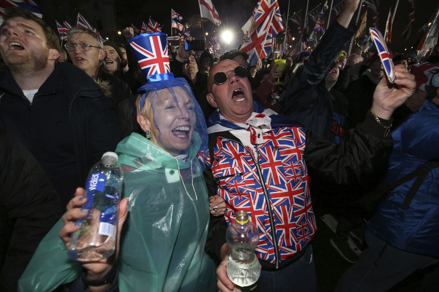 Brexit supporters celebrate during a rally in Parliament square in London, England as Britain left the European Union on Friday, Jan. 31, 2020. Britain officially leaves the European Union on Friday after a debilitating political period that has bitterly divided the nation since the 2016 Brexit referendum.  (Jonathan Brady/PA via AP)