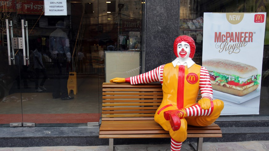 epa04164473 A 'Ronald McDonald' figure sits on a bench outside the newly opened, McDonald's first ever vegetarian-only restaurant near the Golden Temple (not pictured), the holiest of Sikh shrines in Amritsar, India, 12 April 2014. According to  news reports, the McDonald's fast food restaurant in Amritsar solely offers vegetarian food in respect of the sanctity of the Sikh's holy city of Amritsar and area near the holiest Sikh shrine.  EPA/RAMINDER PAL SINGH