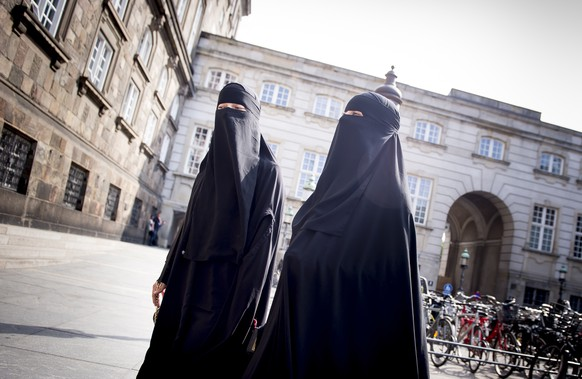 epa06775145 Women wearing the niqab walk in front of the Danish Parliament at Christiansborg Castle in Copenhagen, Denmark, 31 May 2018. A majority in the Danish Parliament adopted a ban wearing niqab or burka in public.  EPA/Mads Claus Rasmussen  DENMARK OUT