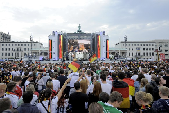German fans gather in front of a giant screen replaying interviews of Germany's World Cup-winning football national team on July 15, 2014, few hours before a victory parade at Berlin's landmark Brandenburg Gate to celebrate their FIFA World Cup title. Germany won their fourth World Cup title, after 1-0 win over Argentina on July 13, 2014 in Rio de Janeiro in the FIFA World Cup Brazil final game .
