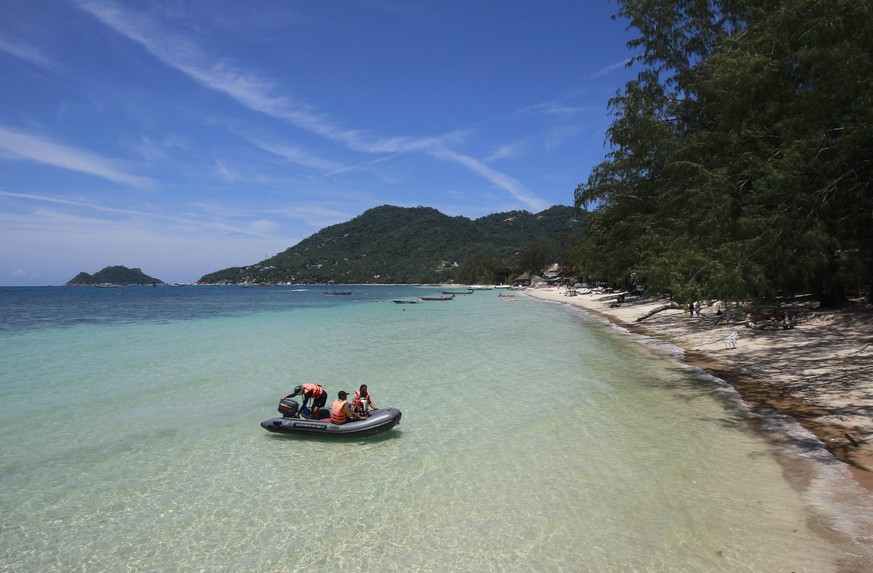 Tourists sit on a boat near the spot where bodies of two killed British tourists were found, on the island of Koh Tao September 20, 2014. The bodies of David Miller and Hannah Witheridge were found early on Monday on a beach on Koh Tao, a southern island known for its coral reefs and diving.    REUTERS/Chaiwat Subprasom  (THAILAND - Tags: CRIME LAW POLITICS TRAVEL)