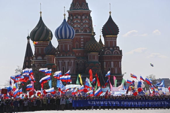 epa05285316 Participants march with a large banner reading 'Unity, solidarity, human rights' during the May Day demonstration on Red Square in Moscow, Russia, 01 May 2016. According to reports, more then 90,000 citizens of Moscow attended the rally. Labor Day or May Day is observed all over the world on the first day of the May to celebrate the economic and social achievements of workers and fight for laborers rights.  EPA/SERGEI ILNITSKY