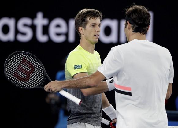 Switzerland's Roger Federer, right, is congratulated by Slovenia's Aljaz Bedene as Federer won their first round match at the Australian Open tennis championships in Melbourne, Australia, Tuesday, Jan. 16, 2018. (AP Photo/Dita Alangkara)
