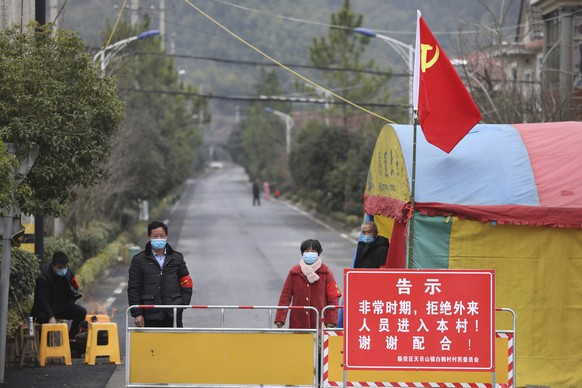Volunteers stand beneath a Communist Party flag as they man a barricade checkpoint at a village in Hangzhou in eastern China's Zhejiang Province, Monday, Feb. 3, 2020. China sent medical workers and equipment to a newly built hospital, infused cash into financial markets and further restricted people's movement in sweeping new steps Monday to contain a rapidly spreading virus and its escalating impact. (Chinatopix via AP)