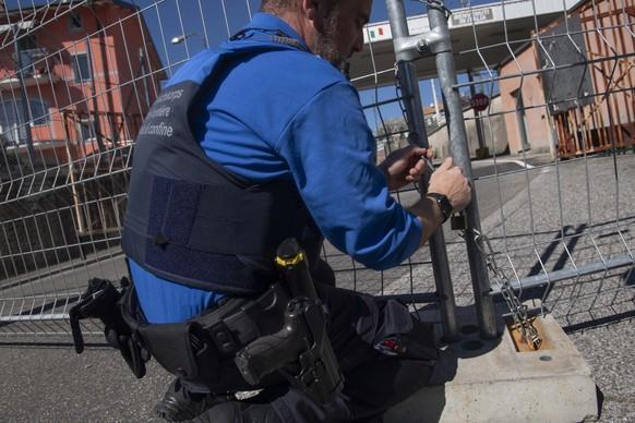 Beamte des Grenzwachkorps schliessen den Grenzübergang San Pietro di Stabio zwischen der Schweiz und Italien mit Gittern und Ketten.
