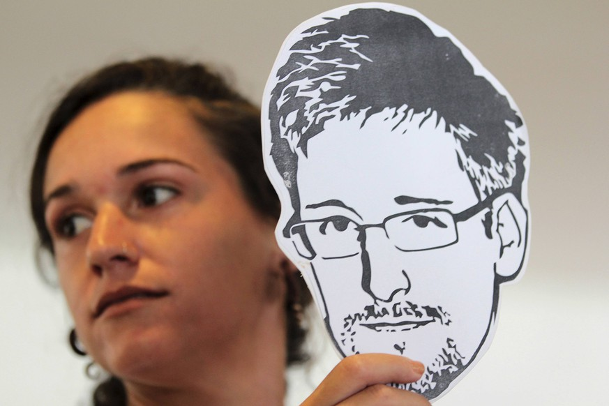 An activist from advocacy group Avaaz holds an illustration of former U.S. spy agency NSA contractor Edward Snowden during a delivery of a petition to the Itamaraty Palace in Brasilia February 13, 2014. The activists said they were delivering over a million signatures from 200 countries to authorities, requesting asylum for Snowden in Brazil. REUTERS/Joedson Alves (BRAZIL - Tags: POLITICS CIVIL UNREST CRIME LAW)