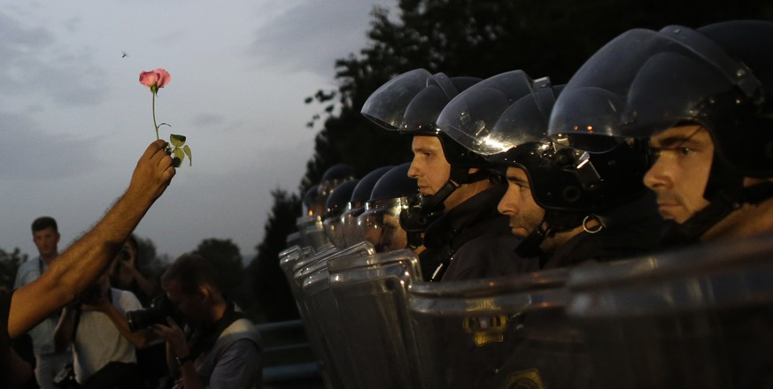A man holds up  a flower as he and a group of refugees and supporters face Slovenian police blocking their entrance to Slovenia, at the border crossing of the Croatian village of Harmica, Friday, Sept. 18, 2015. Hundreds of people have gathered on the Croatian border, chanting and demanding to be let into Slovenia, while 50 Slovenian riot police on the other side are keeping them out. (AP Photo/Markus Schreiber)