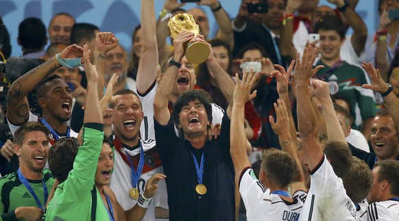 Germany's coach Joachim Loew lifts the World Cup trophy after his team won the 2014 World Cup final against Argentina at the Maracana stadium in Rio de Janeiro July 13, 2014. REUTERS/Kai Pfaffenbach (BRAZIL  - Tags: SPORT SOCCER WORLD CUP)