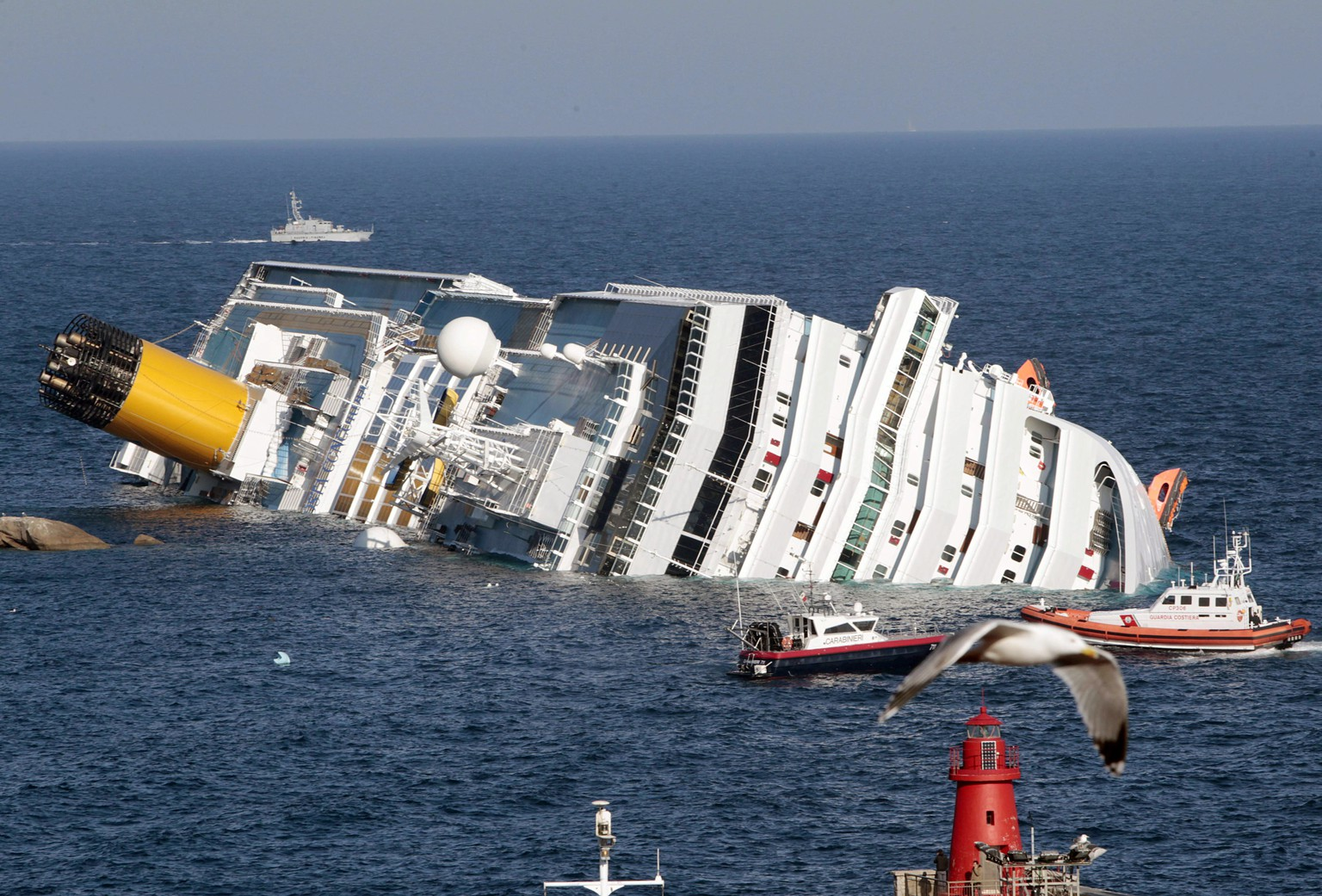 FILE -- In this file photo taken on Jan. 14, 2012, the luxury cruise ship Costa Concordia lays on its side after running aground the tiny Tuscan island of Giglio, Italy. A prosecutor in the trial for the shipwreck of the Costa Concordia contends that 32 people died not because the luxury cruise liner crashed into a reef, but due to