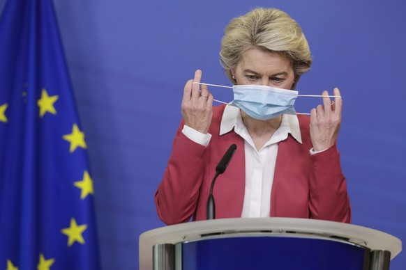 European Commission President Ursula von der Leyen takes off her protective face mask as she prepares to deliver a statement at EU headquarters in Brussels, Tuesday, July 27, 2021. The European Union has achieved a major goal of providing at least one coronavirus shot to 70 percent of adults across the 27-nation bloc but member countries must step up their vaccination rates to combat fast-spreading variants of the disease, the EU's chief executive warned Tuesday. (Stephanie Lecocq, Pool Photo via AP)