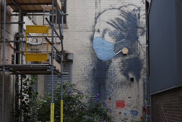 epa08547234 British artist Banksy's work 'Girl with a Pierced Eardrum' is displayed wearing a face covering in Bristol, Britain, 15 July 2020. The work, a parody of 'Girl with a Pearl Earring' by Johannes Vermeer, first appeared in the street artist's home city of Bristol in 2014. In April 2020 the work was modified to appear to be wearing a clinical mask similar to those work by the Britain's National health Service (NHS).  EPA/NEIL HALL