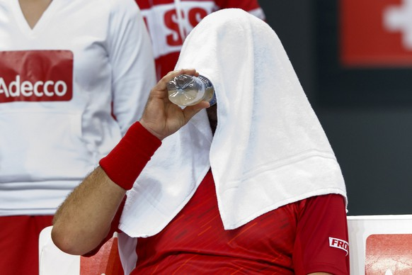 Stanislas Wawrinka, of Switzerland, drinks some water under his towel, during the first single match of the Davis Cup World Group Quarterfinal match between Switzerland and Kazakhstan, at Palexpo, in Geneva, Switzerland, Friday, April 4, 2014. (KEYSTONE/Salvatore Di Nolfi)fi)