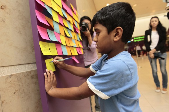 epa04542791 A child writes a post-it note on a board of well wishes for the passengers of the missing AirAsia flight QZ 8501, outside the relatives' holding area at Changi airport in Singapore, 30 December 2014.Floating debris, a possible fuselage, and several bodies were spotted 30 December by rescuers searching for an AirAsia plane with 162 people on board, as officials said they were nearly certain they had found the remains of flight QZ8501. AirAsia Indonesia flight QZ8501 disappeared from radar over the Java Sea after taking off from Surabaya in Indonesia's East Java province en route to Singapore on 28 December morning. AirAsia said 155 of the people on board were Indonesians. The others included three from South Korea, and one each from Singapore, Malaysia, France and Britain.  EPA/WALLACE WOON