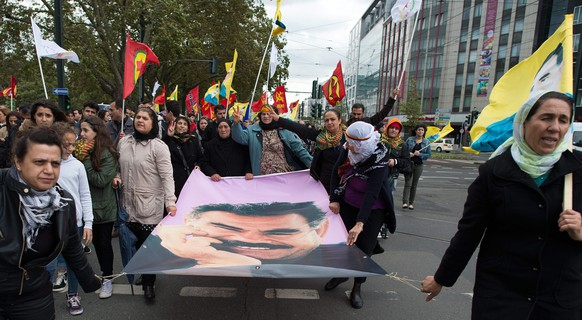 epa04435714 Kurds protest and hold up a portrait of long-term leader of Kurdistan's worker's party (PKK), Abdullah Ocalan during a demonstration calling for support for the Syrian Kurdish town of Ain al-Arab, known as Kobane, currently besieged by the Islamic State (IS), Duesseldorf, Germany, 07 October 2014. Islamic State jihadists pushed into the key Syrian town of Ain al-Arab (Kobane) on the Turkish border, seizing three districts in the city's east after fierce street fighting with its Kurdish defenders.  EPA/FEDERICO GAMBARINI