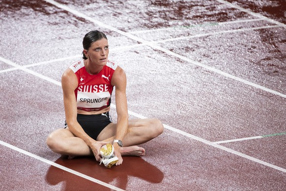 Lea Sprunger of Switzerland sits on the track after the women's athletics 400m hurdles semi final at the 2020 Tokyo Summer Olympics in Tokyo, Japan, on Monday, August 02, 2021. (KEYSTONE/Peter Klaunzer)
