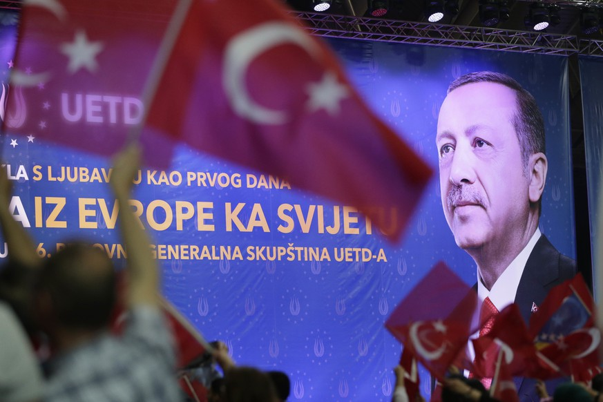 People wave Turkish and Bosnian flags in front of an image of Turkey's president Recep Tayyip Erdogan displayed during a rally, in Sarajevo, Bosnia, on Sunday, May 20, 2018. Turkey's president arrived in the Bosnian capital to address supporters living in Europe, ahead of snap elections in his country. Turkey will vote on June 24, more than a year earlier than scheduled, in parliamentary and presidential elections, ushering in a new system of governance. (AP Photo/Amel Emric)