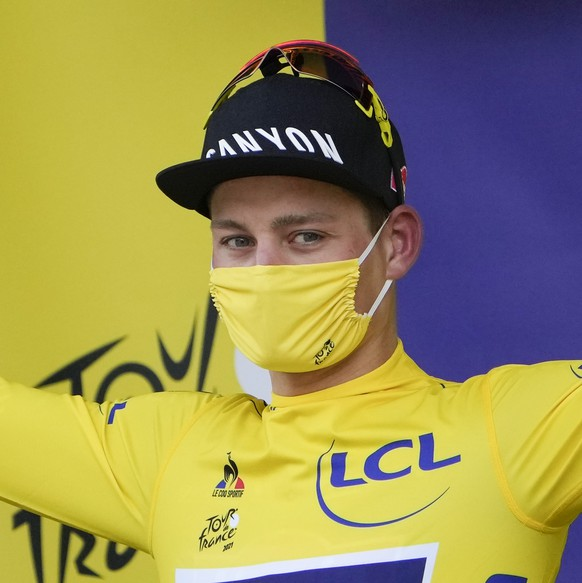 Netherland's Mathieu Van Der Poel, wearing the overall leader's yellow jersey, celebrates on the podium of the third stage of the Tour de France cycling race over 182.9 kilometers (113.65 miles) with start in Lorient and finish in Pontivy, France, Monday, June 28, 2021. (AP Photo/Christophe Ena, Pool)