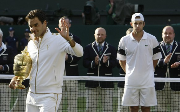 Roger Federer of Switzerland (L) waves as he holds his trophy after defeating Andy Roddick of the U.S. (R) in their Gentlemen's Singles finals match at the Wimbledon tennis championships in London, July 5, 2009.   REUTERS/Stefan Wermuth (BRITAIN SPORT TENNIS) - RTR25CGS