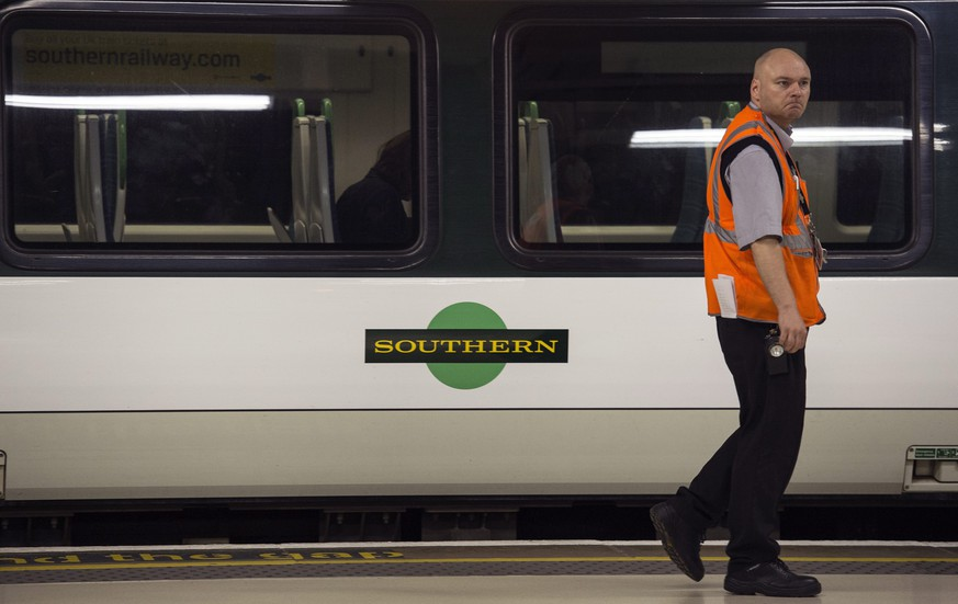 epa05464948 An employee walks past a Southern train during a strike by members of the RMT Union on the Southern rail franchise network, Victoria Station, Central London, Britain, 08 August 2016. The strike is a due to last five days and is the longest strike on British railways since 1968.  EPA/WILL OLIVER