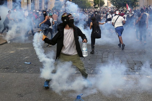 Protesters throw back tear gas canisters towards riot policemen during an anti-government protest, in the aftermath of last Tuesday's massive explosion which devastated Beirut, Lebanon, Monday, Aug. 10, 2020. (AP Photo/Bilal Hussein)