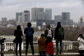 In this photo taken Monday Feb. 8, 2016, tourists look at the view including the HSBC headquarters building standing amongst other skyscrapers in the Canary Wharf business district of London. International bank HSBC said Sunday Feb. 14, it has decided to keep its headquarters in London after considering a move to Hong Kong in response to tougher U.K. banking regulations. (AP Photo/Matt Dunham)