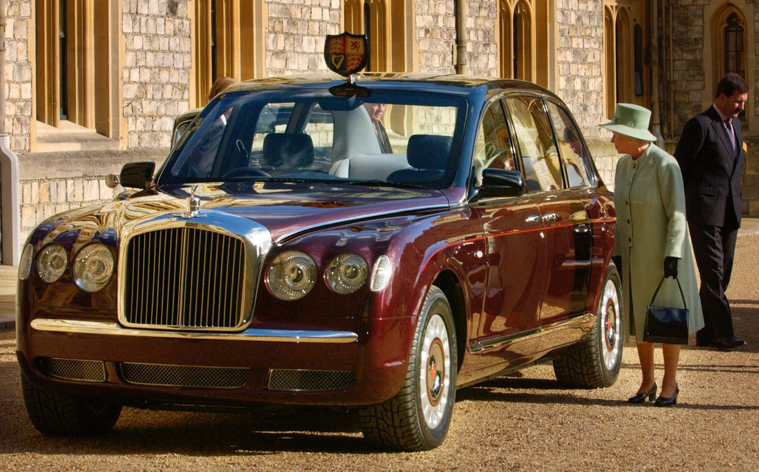 Britain's Queen Elizabeth  stands beside the new Bentley state limousine at Windsor, southern  England, after it was presented to her Wednesday May 29, 2002.  The Bentley in claret and black livery is a Golden Jubilee gift to The Queen from a British based business consortium.  Like the Queen's other official cars, this one has no registration number plate, and carries her personal Coat of Arms at the front, on the roof of the car. (AP Photo / Fiona Hanson, PA) ** UNITED KINGDOM OUT - MAGAZINES OUT -  **