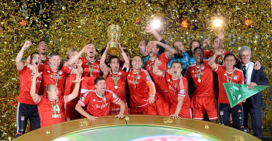 epa03727142 Munich's Thomas Mueller (C) lifts the trophy after winning the German DFB Cup final soccer match between FC Bayern Munich and VfB Stuttgart at the Olympic Stadium in Berlin, Germany, 01 June 2013. Bayern won 3-2.....(ATTENTION: The DFB prohibits the utilisation and publication of sequential pictures on the internet and other online media during the match (including half-time). ATTENTION: BLOCKING PERIOD! The DFB permits the further utilisation and publication of the pictures for mobile services (especially MMS) and for DVB-H and DMB only after the end of the match.)  EPA/BERND WEISSBROD