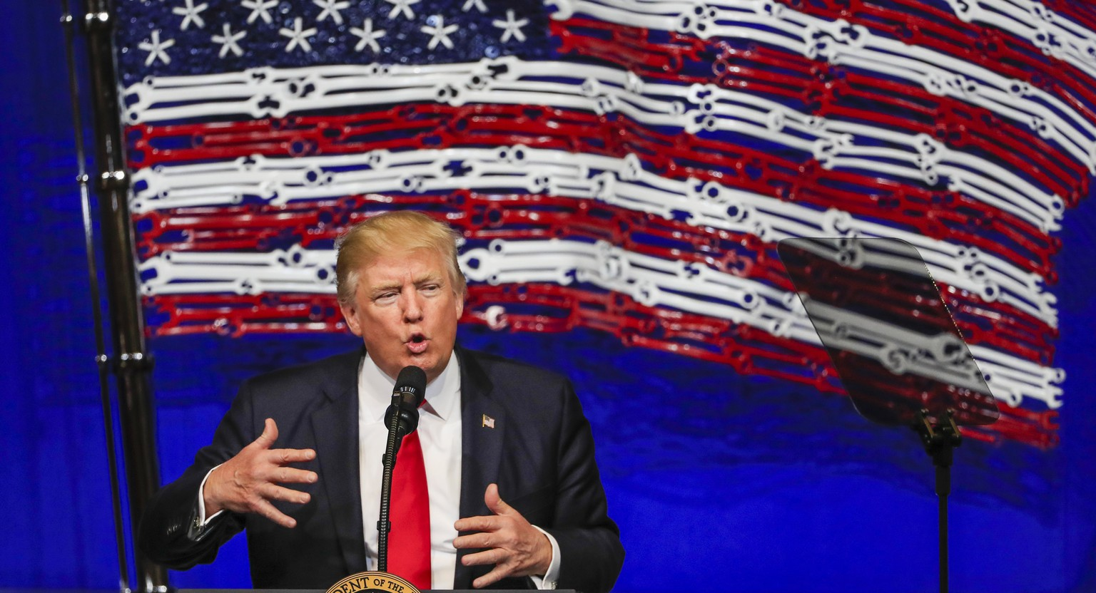 epa05914048 US President Donald J. Trump gestures a he speaks in front of an American flag made of tools at the Snap-on Tools headquarters in Kenosha, Wisconsin, USA, 18 April 2017. Trump spoke on his plan to 'Buy American - Hire American' and signed an executive order to protect American workers and make it harder for foreign contractors to bid on US government endeavors according to administration officials.  EPA/TANNEN MAURY