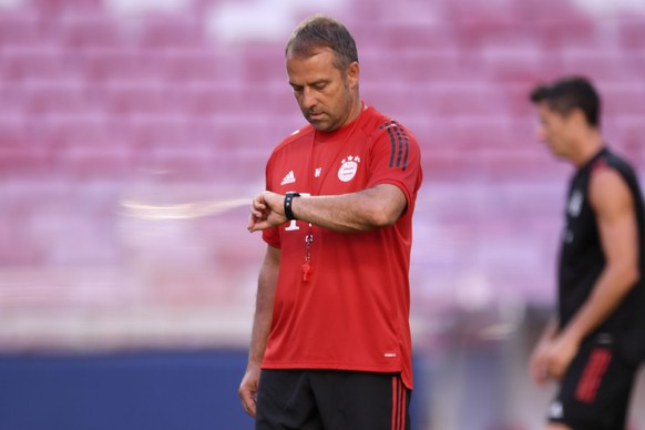 Bayern's coach Hans-Dieter Flick checks his watch during a training session at the Luz stadium in Lisbon, Saturday Aug. 22, 2020. Bayern Munich will play PSG in the Champions League final soccer match on Sunday. (David Ramos/Pool via AP)