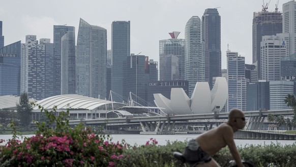 epa09013609 A cyclist rides past the skyline of the financial district in Singapore, 15 February 2021. Singapore has reported a 5.4 percent contraction in its economy in 2020, above advanced estimates that experts had forecasted. The recession, caused by lockdowns and travel restrictions due to the coronavirus disease (COVID-19) pandemic, is still the worst in Singapore's history.  EPA/WALLACE WOON