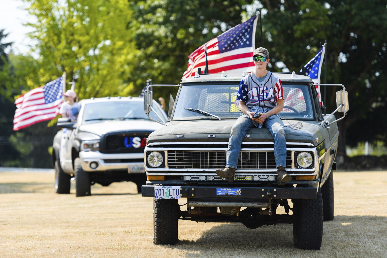 Riley Brumeister, 18, of Gresham, attends his first Trump rally atop the hood of his 1970 Ford F-250, at Clackamas Community College in Oregon City, Ore., Monday, Sept. 7, 2020. (AP Photo/Michael Arellano)