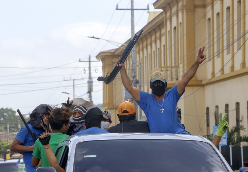 Heavily armed pro-government militia flash victory signs as they occupy the Monimbo neighborhood of Masaya, Nicaragua, Wednesday, July 18, 2018. On Tuesday, Nicaraguan government forces retook the symbolically important neighborhood that had recently become a center of resistance to Ortega's government. (AP Photo/Alfredo Zuniga)