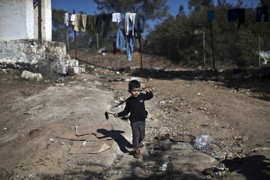 A child plays outside the migrant and refugee registration camp in Moria, on the island of Lesbos, Greece, Wednesday, Nov. 4, 2015. Dozens of overcrowded inflatable dinghies and wooden boats reach Greek islands daily, even during bad weather, and hundreds have drowned as their overloaded and unseaworthy boats overturned or sank. (AP Photo/Marko Drobnjakovic)