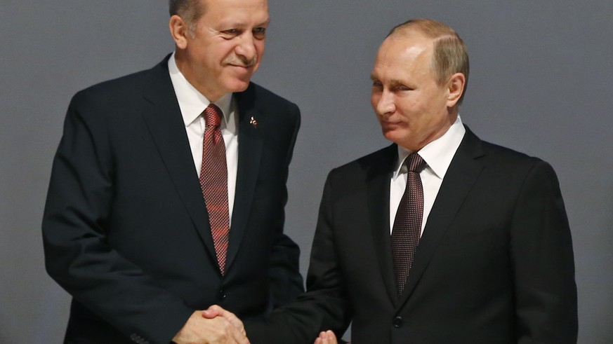Turkey's President Recep Tayyip Erdogan, left and Russian President Vladimir Putin, right,  shake hands following the group photo at the World Energy Congress, in Istanbul, Monday, Oct. 10, 2016. Putin met Erdogan as the two push ahead with steps toward normalizing ties that were strained by Turkey's downing of a Russian warplane near the border with Syria last year.(AP Photo/Emrah Gurel)