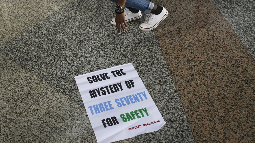 epa05657554 Malaysian Grace Subathirai Nathan (top, obscured), whose mother Anne Daisy was on board missing flight MH370, leaves a banner on the ground during a press conference at Kuala Lumpur International Airport in Sepang, Malaysia, 03 December 2016, before her trip to Madagascar. Family members of passengers onboard Malaysia Airlines Flight MH370, Malaysian Grace Subathirai Nathan, Jiang Hui and Bai Shuan Fu of China, mounted a debris-hunting trip to Madagascar aimed at searching for clues to what happened to the plane that went missing on 08 March 2014 while en route from Kuala Lumpur to Beijing with 239 people on board. Investigators have identified debris collected, believed to belong to the wreckage of the missing airliner, all found off Africa's east coast. In a Facebook statement, Malaysian Grace Subathirai Nathan said the relatives will travel to Madagascar to further the search with six other next-of-kin.  EPA/FAZRY ISMAIL