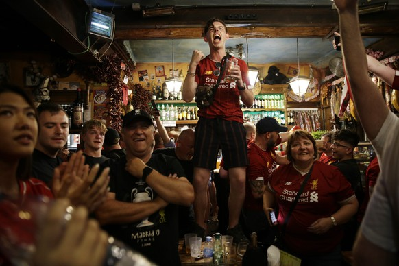 Liverpool supporters celebrate the victory in a pub at the final whistle of the Champions League final soccer match between Tottenham Hotspur and Liverpool at the Wanda Metropolitano Stadium in Madrid, Saturday, June 1, 2019. Liverpool won 2-0. (AP Photo/Andrea Comas)
