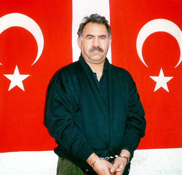 Kurdish rebel leader Abdullah Ocalan poses in front of Turkish flags before being interrogated by Turkish officials at the prison-island of Imrali in this image provided by the Turkish Intelligence Service on Feb.18, 1999. A Turkish court upheld a ruling that rejected a request to retry imprisoned Kurdish rebel leader Abdullah Ocalan, officials said Wednesday, July 26, 2006. Ocalan, who led the Kurdistan Workers Party, or PKK, demanded a retrial in late February but his request was rejected in May. Another court on Tuesday upheld that decision, saying recent amendments in the penal code would not benefit Ocalan. (AP Photo/Turkish Intelligence Service-MIT/Anatolia)