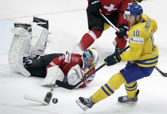Switzerland's goaltender Leonardo Genoni (L) defends against Sweden's Joakim Lindstrom during their Ice Hockey World Championship game at the O2 arena in Prague, Czech Republic, May 9, 2015.   REUTERS/David W Cerny