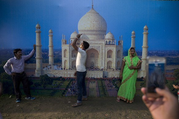 In this Monday, Aug. 15, 2016 photo, Indians get themselves photographed infront of a photo of Taj Mahal at a food and culture festival being held near the India Gate war memorial as part of Independence Day celebrations in New Delhi, India. India gained its independence from British colonial rule on this day in 1947. (AP Photo/Tsering Topgyal, File)