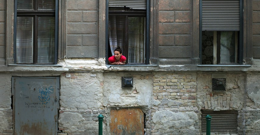A Gypsy woman looks looks out from her window in Budapest's gritty 8th district on May 18, 2015 in Budapest, Hungary. Roma volunteers provide walking tours for non Roma visitors with an aim to break down prejudices and stereotypes, about this neighborhood of the city which is not typically featured in guidebooks. (AP Photo/Bela Szandelszky)