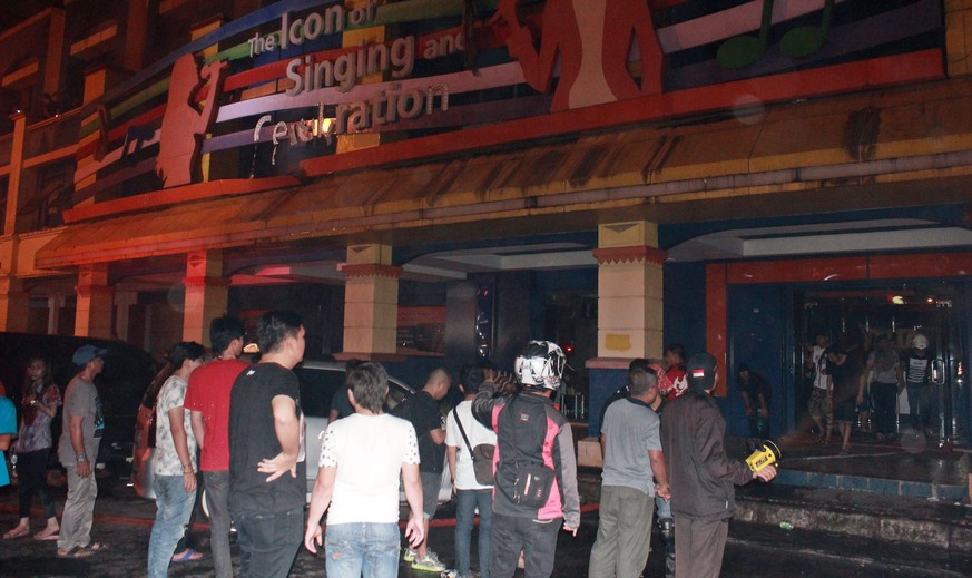 epa04994639 Indonesian rescuers and residents gather after fire hit a karaoke bar in Manado, North Sulawesi, Indonesia, 25 October 2015. At least twelve people were killed in a fire at a karaoke bar early 25 October and dozens were hospitalized, police said.  EPA/TONNY RAUNG
